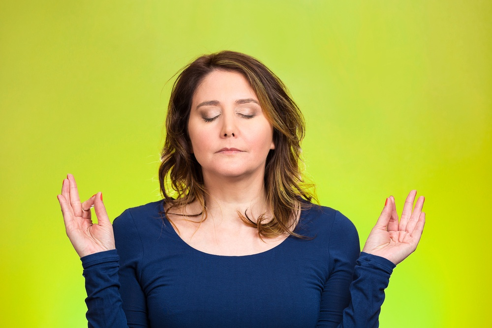 Closeup portrait peaceful young woman relaxing, meditating, in zen mode, isolated green background. Positive human emotions, facial expressions, attitude, life perception, situation, symbols, approach