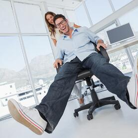 Smiling designers having fun with on a swivel chair in their office.jpeg