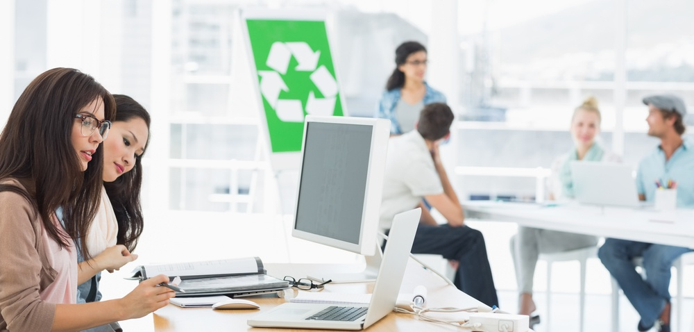 Casual group artists working at desks with recycling sign in background at a bright office.jpeg